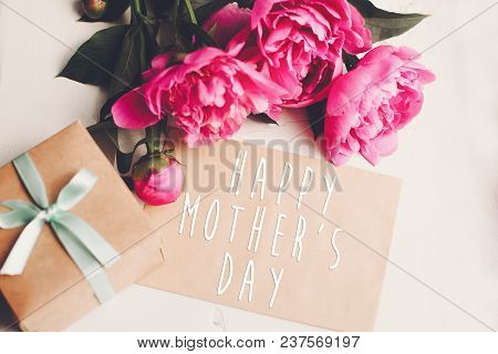 Happy Mother's Day Text On Craft Card And Pink Peonies Bouquet With Gift Box On Rustic White Wooden