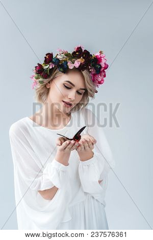 Beautiful Girl Posing In Floral Wreath With Alive Butterfly In Hands, Isolated On Grey