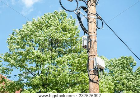 Phone Line. Electric Wires On Wooden Street Pole With Internet Or Cell Phone Communication Boxes And