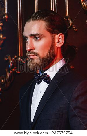 Portrait of a well-dressed imposing man in elegant suit posing in apartments with luxurious classic interior. Men's beauty, fashion. Hair styling, barbershop.