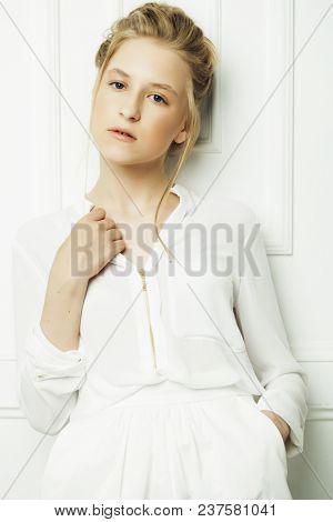 Cute little girl in white dress over white background