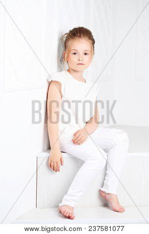 Children's fashion. Beautiful pensive serious blonde girl