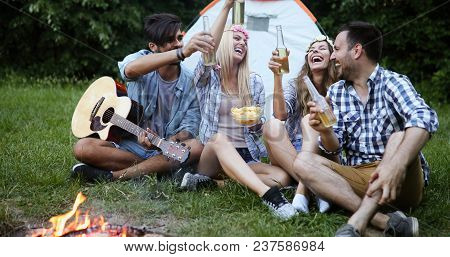 Group Of Friends Camping, Sitting Around Camp Fire, Playing Guitar