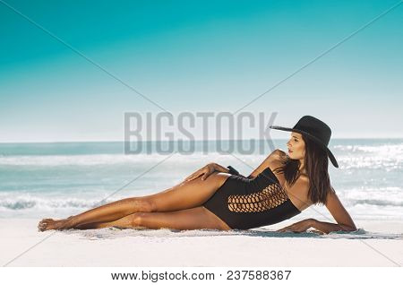 Fashion young woman in black swimsuit and straw hat lying on side at beach. Beautiful tanned girl lying on sand. Attractive girl wearing glamour swimwear on tropical beach while sunbathing.
