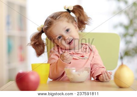 Child Girl Eating Yoghurt With Fruits At Home, Nursery Or Daycare Centre