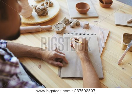 Unrecognizable male ceramist working on design of future handicrafts while sitting at wooden table with pencil and sketchbook