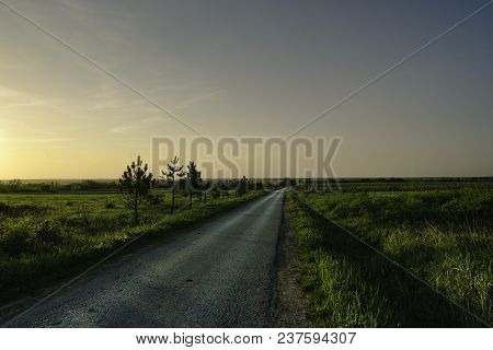 Lonely Road In Countryside. Lonely Road At Sunset. Green Field And Late Sunlight On The Road. Road I