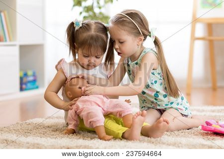 Two Children Girls Playing Doctor With A Doll In Kindergarten