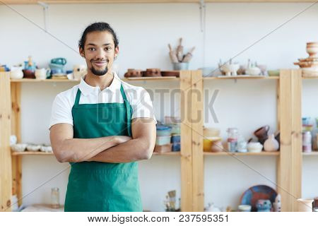 Portrait of handsome mixed race craftsman standing in pottery workshop with crossed hands and smiling at camera