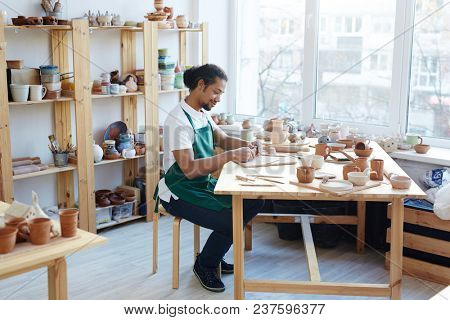 Young handsome mixed race craftsman in apron making clay utensil and smiling while sitting at table in workshop