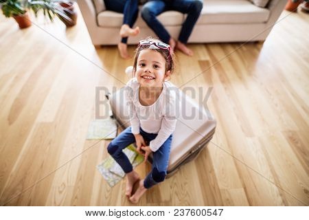 A Small Girl With Unrecognizable Parents Packing For A Holiday. A Child Sitting On A Suitcase.