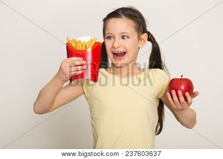 Happy Little Girl Holding A Bag Of Fries And Apple Isolated On White Background. Fast Food Against H