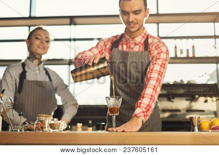 Portrait Of Two Young Bartenders Preparing Fresh Bracing Drink At Coffee House Interior. Occupation