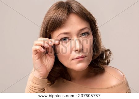 Close Up Of Nice Woman Touching Her Eyelashes. Wearing Light Beige Blouse. Mid Age Woman Over 35 Yea