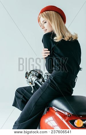 Attractive Young Woman In Black Clothes Posing By Red Motorcycle Isolated On Grey