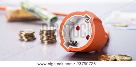 Socket With Coins And Banknotes In The Background