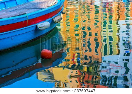 Blue boat and colorful reflection on the water surface in small town of Camogli, Italy.