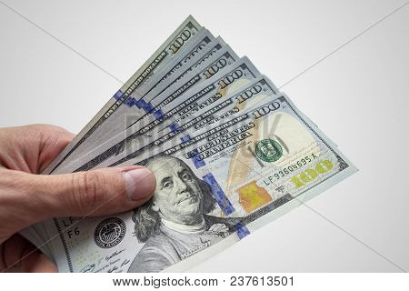 Dollars, Closeup Photo Of Hand Holding One Hundred Dollar Banknotes On White Background.