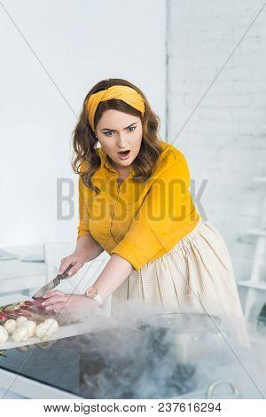 Shocked Beautiful Woman Looking At Burning Pan On Electric Stove At Kitchen