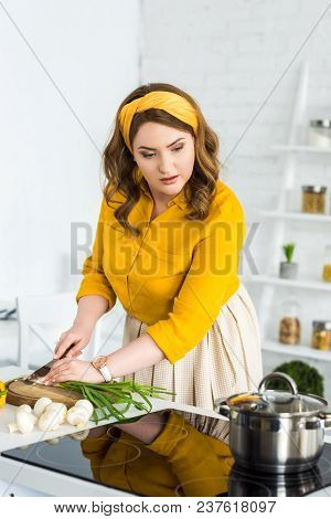 Beautiful Woman Cutting Green Onion And Looking At Pan On Electric Stove