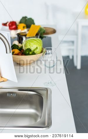 Empty Wineglass And Vegetables On Kitchen Counter