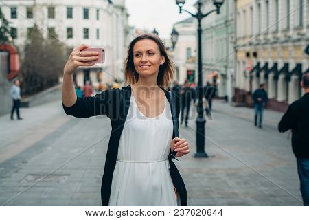 Beautiful Girl Makes Picture In European City. Selfie Is In Moscow. Traveler Makes Selfie Around Old