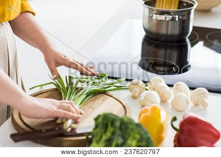 Cropped Image Of Woman Putting Green Onion On Cutting Board At Kitchen