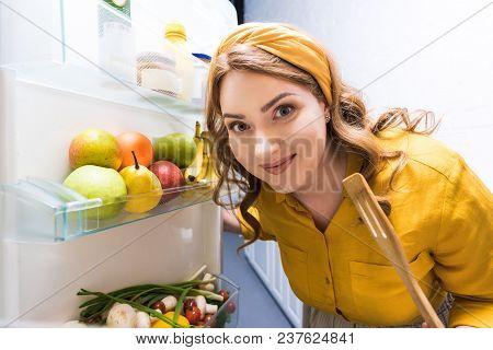 Beautiful Woman Opening Fridge And Holding Wooden Spatula At Kitchen