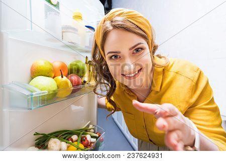 Beautiful Smiling Woman Reaching Hand In Fridge At Kitchen
