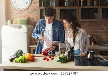 Happy Couple Preparing Dinner Together In Their Loft Kitchen At Home. Making Vegetable Salad.