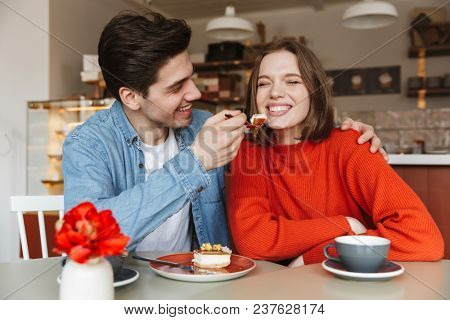 Family portrait of happy couple eating sweets while man feeding girl with tasty cake in cafe