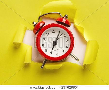 Red Alarm Clock Showing Up From Torn Yellow Paper At White Background. Time Is Our Most Precious Res