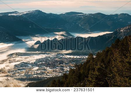 Beautiful View Of A Village In A Valley On A Winter Morning, With Fog Covering The Valley And Part O
