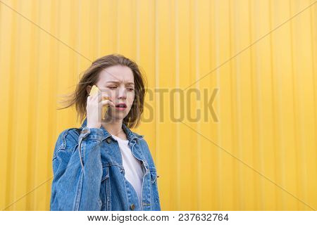 An Emotional Girl In A Denim Jacket Speaks By Telephone On The Background Of A Yellow Wall. A Surpri