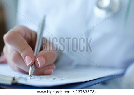 Cropped Image Of Female Doctor's Hands Filling Patient Registration Or Prescription Form. Healthcare