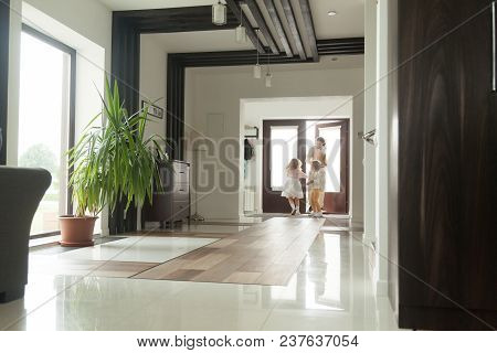 Happy Father And Kids Opening Door Entering Big Modern House Coming Back Home Holding Paper Bag With