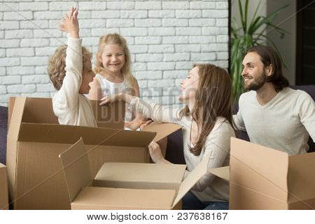 Happy Kid Boy Jumping Out Of Cardboard Box Playing With Family While Packing Together Preparing To R