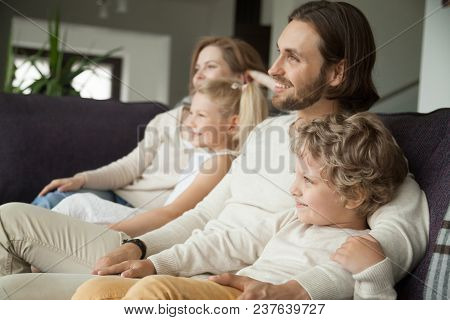 Happy Family With Children Sitting On Sofa Watching Tv, Young Parents Embracing Son Daughter Relaxin