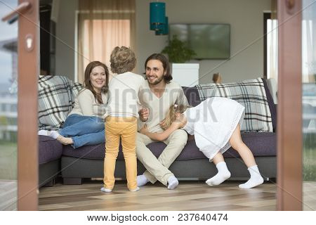 Happy Cheerful Family Playing At Home On Weekend, Active Kids Having Fun With Parents Relaxing On So