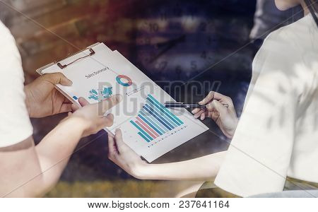 Young Businesspeople Pointing And Working With Business Graph Report While Standing At Office
