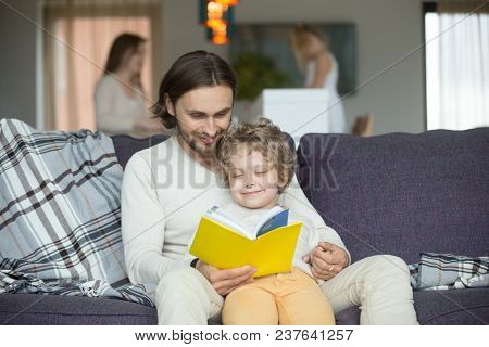 Happy Dad And Son Having Fun With Book Together, Loving Daddy Teaching Preschool Boy To Read, Daddy