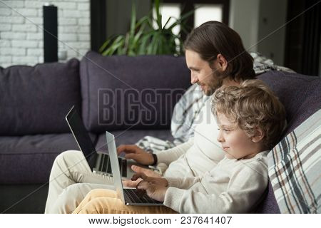 Curious Smiling Child Typing On Laptop Looking At Screen With Dad On Sofa, Daddy And Little Boy Usin