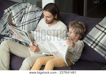 Cute Kid Son Holding Newspaper Sitting On Sofa With Dad, Curious Funny Clever Boy Pretending Reading