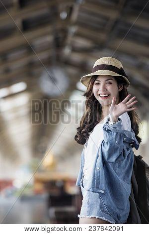 Asian Backpack Traveler Woman Smiling And Waving Hand At Train Station Platform, Summer Holiday Trav