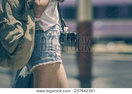 Cropped Image Of Young Woman Traveler In Short Blue Jeans With Backpack And Vintage Camera Standing