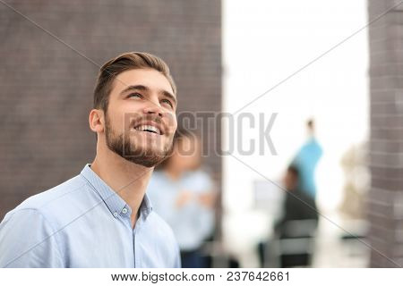 Smiling businessman in profile on office background,