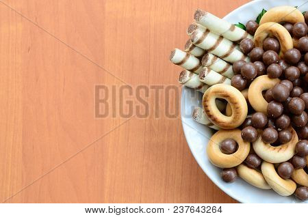 Crispy Tubules, Chocolate Melting Balls And Bagels Lie In A White Plate On A Wooden Table. Mix Of Va