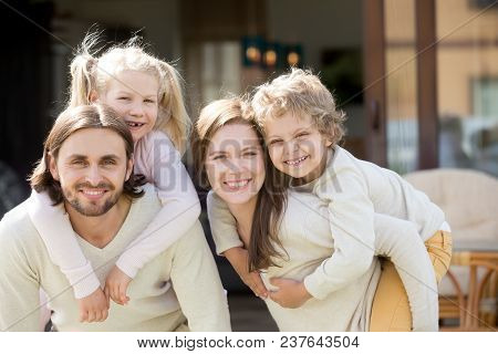 Happy Parents Piggybacking Son And Daughter Outdoors, Smiling Couple With Cute Children Have Fun Tog