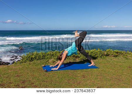 A Woman Practicing Yoga Along The Scenic Maui Coast