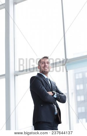 portrait of confident businessman looking out the window of the office.